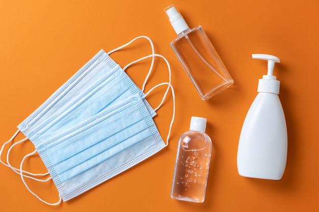 医療用保護具、フェイスマスク、消毒ジェル、スプレー、オレンジ色の背景に液体ハンドソープ