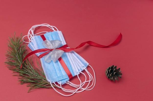 赤いギフトリボンで結ばれた医療用保護フェイスマスククリスマスパインの枝とコーン