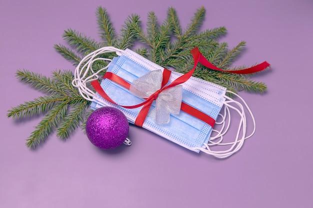 赤いギフトリボンモミの枝とクリスマスボールで結ばれた医療用保護フェイスマスク