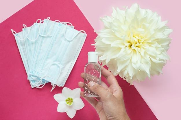 医療用防護マスクと花の近くの消毒剤