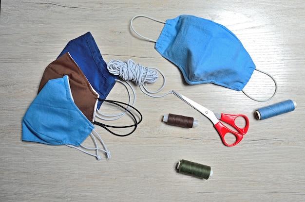 テキスタイルから手作りされた医療用保護マスクブルーカラー。抗ウイルスマスク、個人用保護具。コロナウイルスの概念。