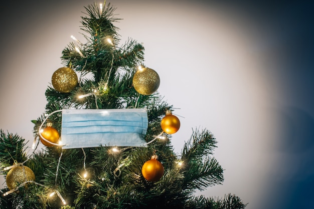 Medical protective mask hanging on christmas tree decorated with shiny balls and glowing garland. celebrating winter holidays safely during coronavirus pandemic. covid and happy new year concept.