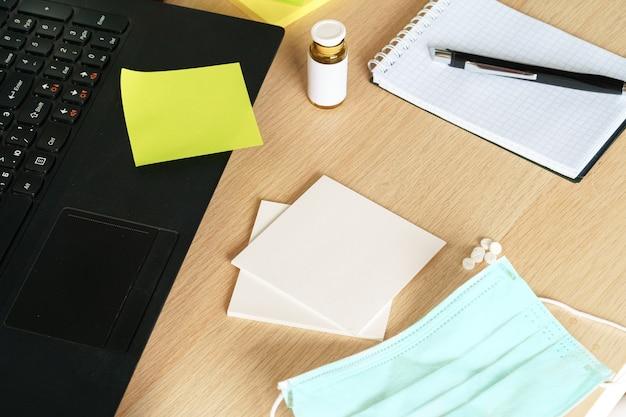 オフィステーブルの医療用保護マスク。コロナウイルス拡散防止の概念。家にいる