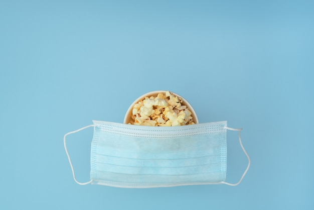 Medical protective mask placed on the cup of tasty popcorn on blue.