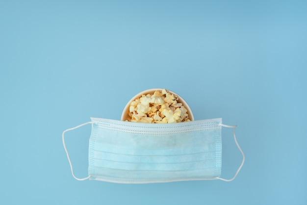 Медицинская защитная маска помещена на чашку вкусного попкорна на синем.