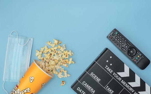 Medical protective mask, popcorn, movie clapper board, tv remote on blue.