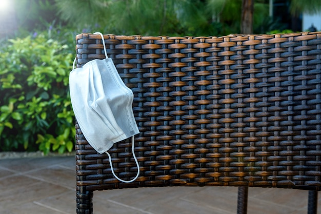 Medical protective mask on a wicker rattan chair in the summer during the covid-19 coronavirus.