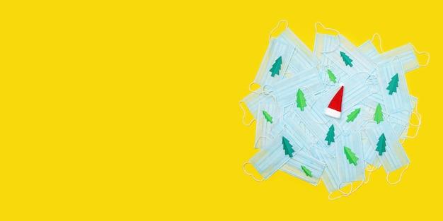 Медицинские защитные маски от коронавируса, украшенные елочной бумагой и шапкой деда мороза. плоская планировка, копия пространства. концепция коронавируса. длинный широкий баннер
