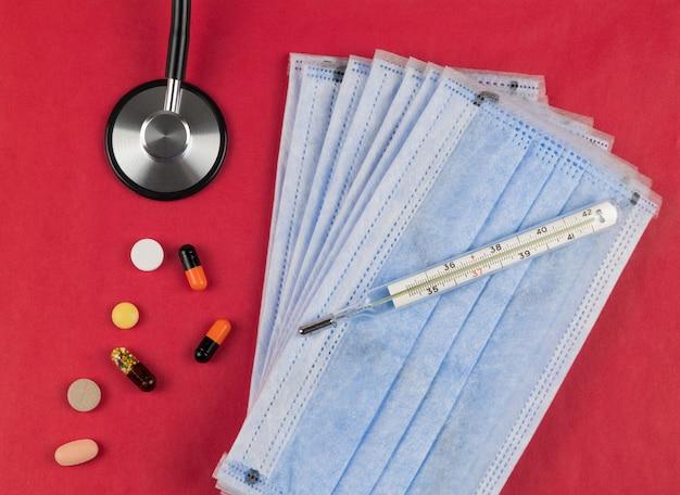 タブレット、温度計、聴診器を備えた赤い背景の医療用保護マスク..コロナウイルス保護の概念