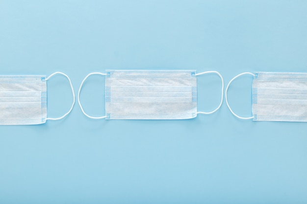 青の背景に医療用防護マスク。使い捨ての外科用フェイスマスクが口と鼻を覆っています。ヘルスケアのコンセプト