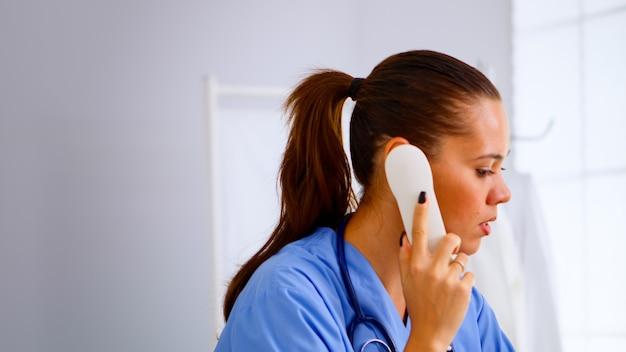 病院の患者からの電話に応答する医療受付係が予約を確認します。医療制服を着た医療医師、遠隔医療コミュニケーションを支援する医師看護助手