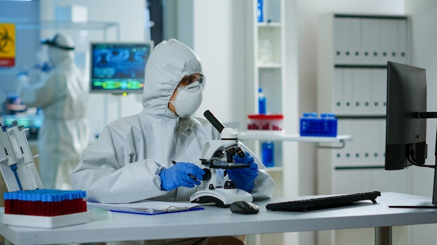 Medical research scientist conducting dna experiments under microscope wearing protection suit and writing informations on clipboard. chemist using high tech for vaccine development against covid19