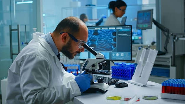 Medical research scientist conducting vaccine development under digital microscope in a biological applied science laboratory