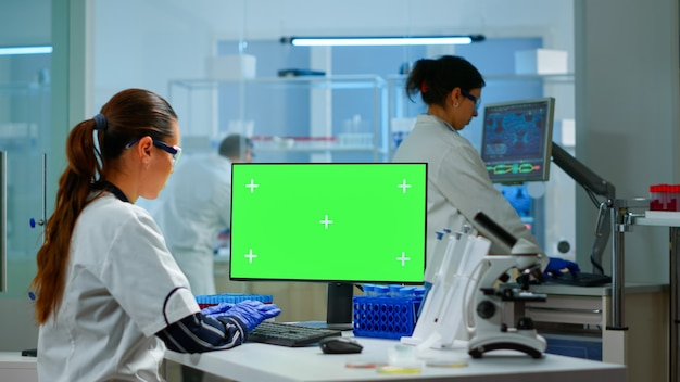 Medical research scientist working on pc with green screen mock up template in applied science laboratory. engineers conducting experiments in background, examining vaccine evolution using high tech