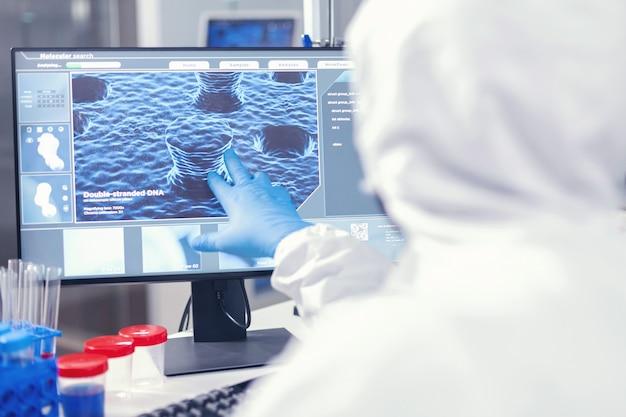 Одетый медицинский исследователь, анализирующий эволюцию коронавируса, указывая на экран в современном медицинском учреждении. инженеры лаборатории проводят эксперимент по разработке вакцины против вируса covid19