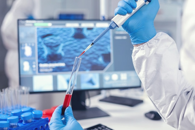 Medical researcher dripping blood into a test tube from a micropipette. doctor working with various bacteria and tissue, pharmaceutical research for antibiotics against covid19.