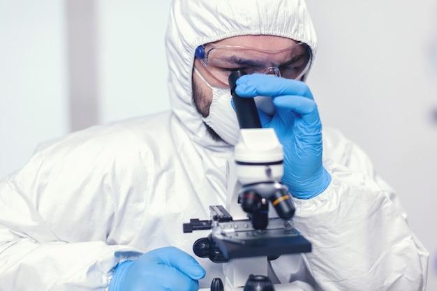 Медицинский исследователь, глядя через микроскоп на образец вируса, одетый в костюм ppe. ученый в защитном костюме сидит на рабочем месте, используя современные медицинские технологии во время глобальной эпидемии.