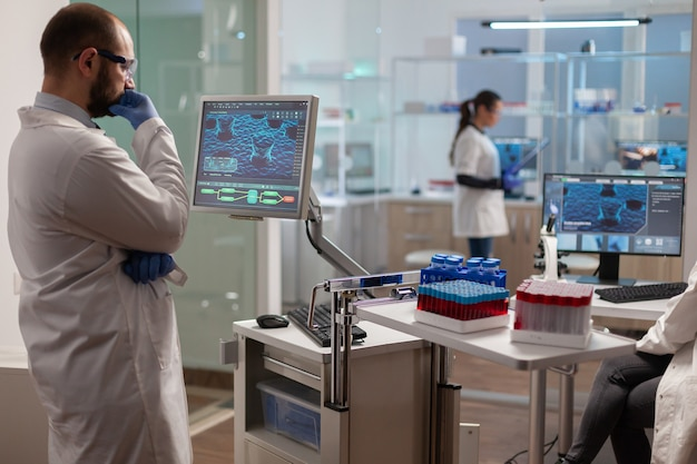 Medical researcher in scientific laboratory analyzing dna sample. chemical scientis analyzing vaccine on screen examining vaccine development using high tech researching treatment.
