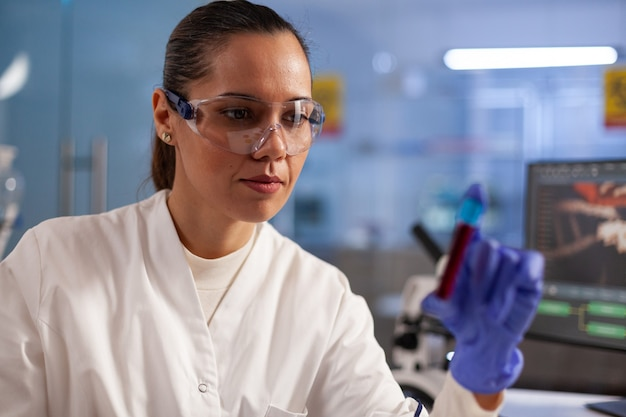 Medical researcher scientist analyzing blood jar sample for development test in chemical laboratory. professional woman with lab coat, glasses and gloves finding treatment for healthcare