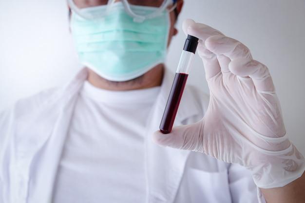 의료 연구원은 코로나 바이러스 환자의 혈관을 보여주는 세균을 막기 위해 마스크와 라텍스 장갑을 착용합니다