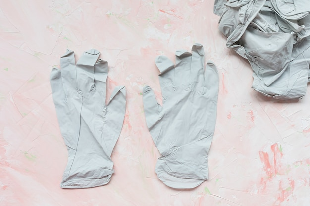 Medical rubber gloves on pink background coronavirus covid and surgery protection concept