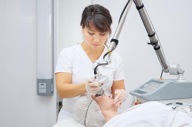 医療サロンの従業員は、ネオジムレーザーを使用して傷跡を取り除きます