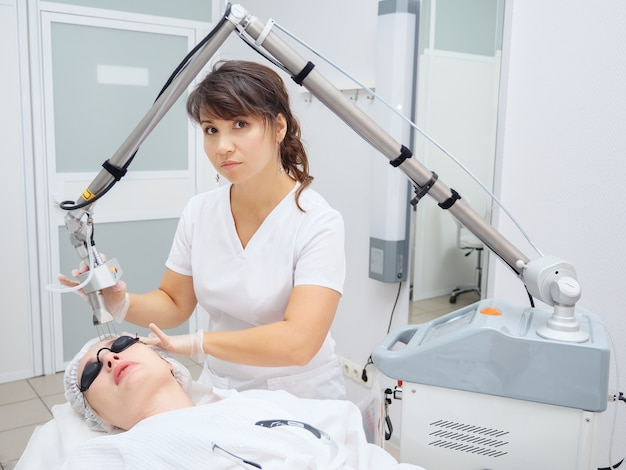 Medical salon woman employee uses effective neodymium laser removing unwanted scars on young patient face