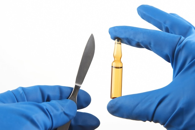 파란색 장갑을 끼고 손에 주사를위한 의료 메스와 바이알