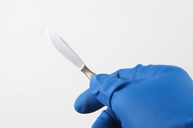 青い手袋を着用して手に医療メス