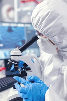 Ученый-медик анализирует образец на стекле, глядя через микроскоп. химик-исследователь во время глобальной пандемии с проверкой образца covid-19 в биохимической лаборатории