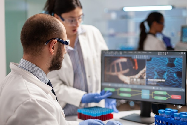 Medical scientist conducting vaccine research against new virus in modern equipped laboratory. chemists stuff analysing virus evolution using high tech technology for treatment research.