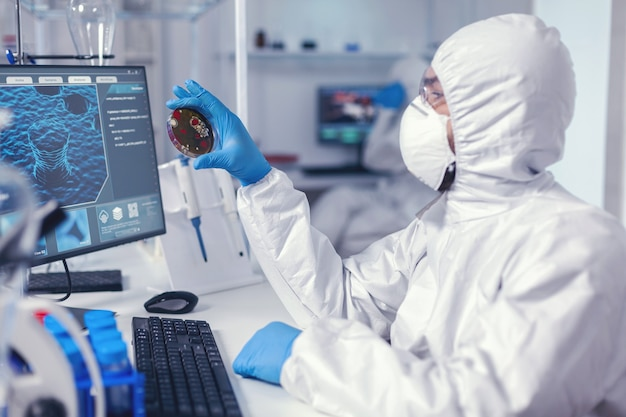 Medical scientist holding petri dish studying virus sample dressed in bacteriological suit doctors analysing vaccine evolution using high tech researching diagnosis against covid19 virus.