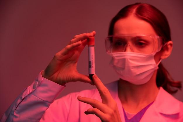 Ученый-медик в маске и защитных очках держит пробирку во время исследования образца крови инфицированного пациента в красном свете