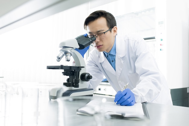 Medical scientist using microscope