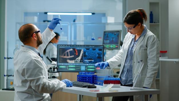 샘플이 포함된 테스트 튜브를 들고 있는 현대적인 실험실에서 dna 스캔 이미지로 작업하는 의료 과학자. 백신 개발을 위한 첨단 화학 도구를 사용하여 백신 진화를 조사하는 팀
