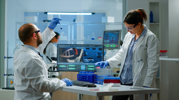 Medical scientist working with dna scan image in modern equipped laboratory holding test tube with sample. team examining vaccine evolution using high tech and chemistry tools for vaccine development