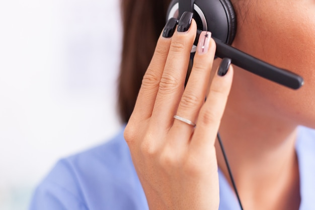 마이크가 달린 헤드폰을 끼고 환자와 대화를 나누는 의료 비서. 여성 간호사, 상담 중 아픈 사람과 통화 검사 중 의사, 약.