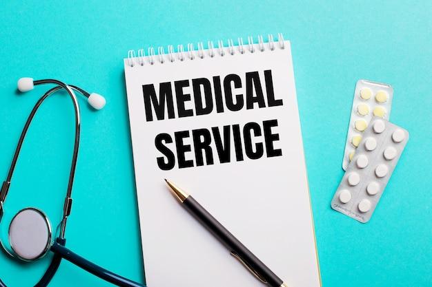 聴診器の近くの白いメモ帳、水色の表面のペンとピルで書かれた医療サービス