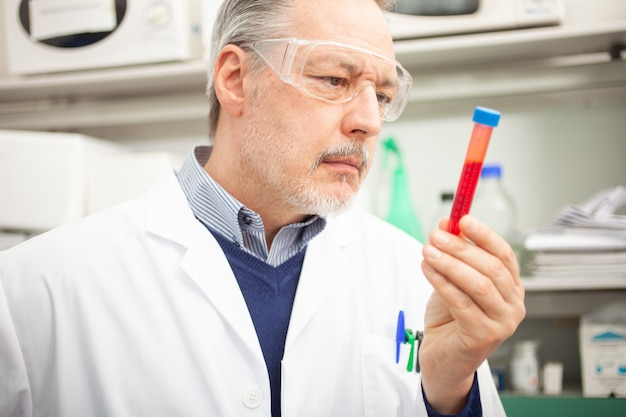 Medical sientist researcher looking at a blood tube, coronavirus blood test