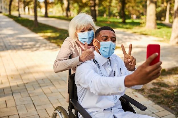 医療専門家と年金受給者が親指を立ててピースサインをしながら赤いスマートフォンで一緒に写真を撮る