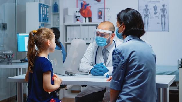 Медицинский специалист исследует рентгеновский снимок ребенка в больнице во время пандемии. врач педиатр с защитной маской, предоставляющий медицинские услуги, консультации, рентгенологическое лечение в медицинском кабинете.
