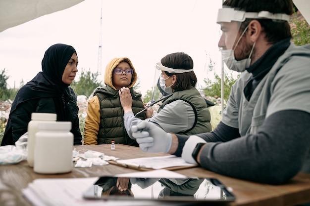 女の子の健康状態を調べ、屋外でイスラム教徒の母親と話している医療専門家