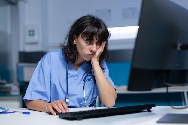 책상에서 잠들고 컴퓨터를 사용하는 의료 전문가