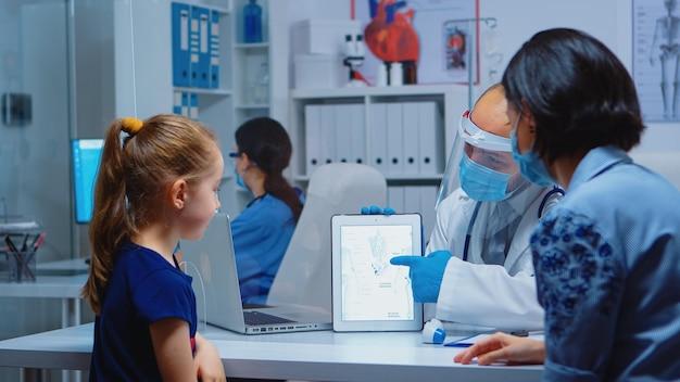 診療所の机の上に座っているタブレットを使用してスケルトンを提示する医療専門家。 covid-19の間にヘルスケアサービス、相談、治療を提供する保護マスクを持つ小児科医