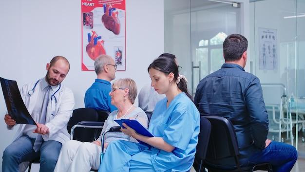 Медицинский персонал обсуждает диагноз с пожилой женщиной-инвалидом в инвалидной коляске в коридоре больницы. старик ждет медицинского обследования. медсестра делает заметки в буфере обмена.