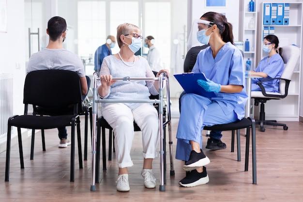 의료진은 코로나바이러스에 대한 얼굴 마스크를 쓰고 병원 대기실에서 보행기를 들고 있는 장애인 노인 여성과 치료에 대해 논의합니다.
