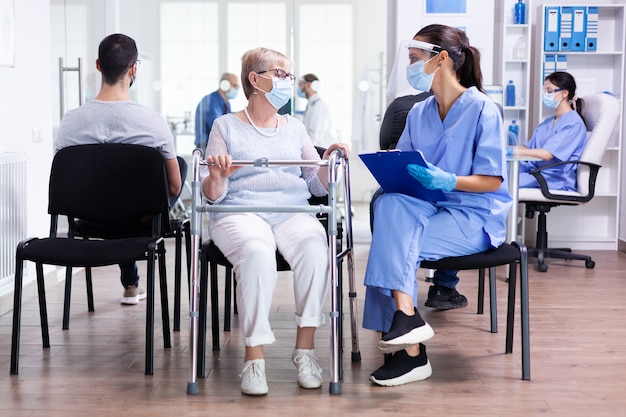 Medical staff discussing treatment with disabled senior woman carrying a walking frame in hospital waiting room wearing face mask against coronavirus