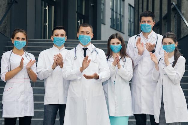 코로나 바이러스와 싸우고있는 병원의 의료진은 국민과 경찰의 지원에 박수를 보냅니다. 얼굴 마스크와 의사의 그룹입니다. 코로나 바이러스 및 의료 개념.
