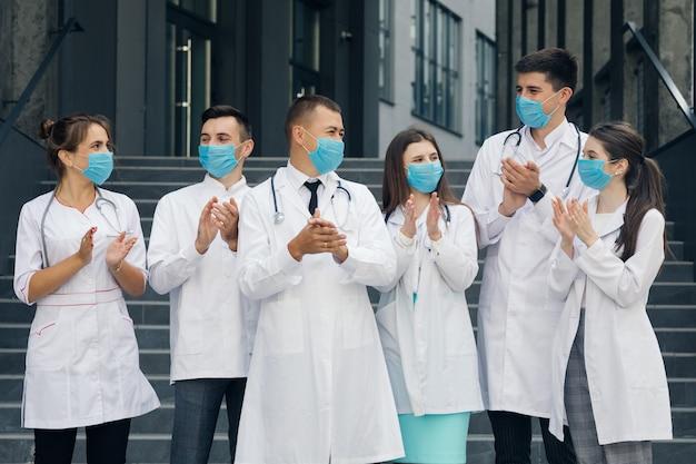 Медицинский персонал больницы, который борется с коронавирусом, аплодирует людям за их поддержку. состояние тревоги. корона вирус и концепция здравоохранения. врачи с масками для лица.