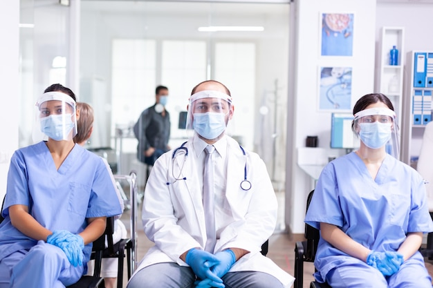 安全対策としてコロナウイルスの発生に対するフェイスマスク保護を身に着けているクリニック待合室の医療スタッフ